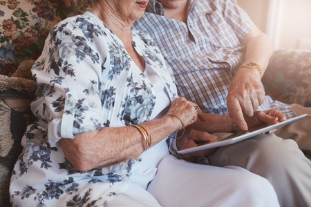 comfortable: Cropped shot of senior couple sitting together using touch screen computer. Focus on hands of elderly couple and digital tablet.