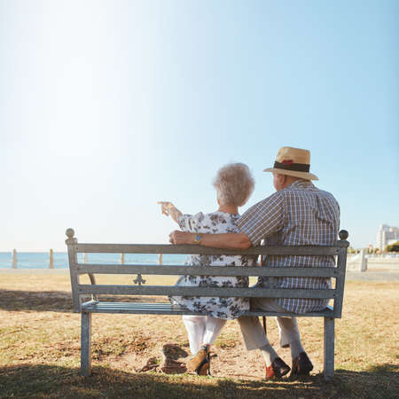 benches: Rear view of senior couple relaxing on a bench with woman pointing out to sea. Retired man and woman sitting on a bench outdoors and enjoying the view.
