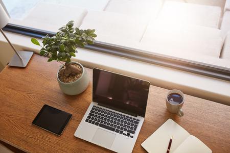 vysoký úhel pohledu: Pohled shora na přenosný počítač, digitální tablet, hrnkové rostliny, deník a šálek kávy na dřevěném stole. Moderní pracovní stůl u okna. Reklamní fotografie