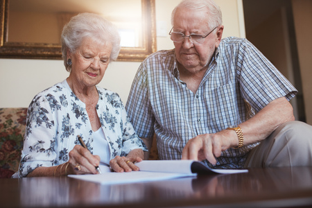 Indoor shot of mature couple at home signing documents together. Senior man and woman sitting on sofa doing retirement paperwork. Banque d'images