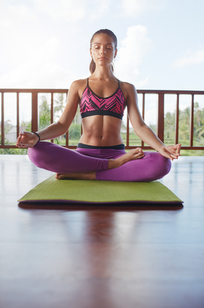 closed club: Vertical shot of fitness female meditating in health club. Woman in yoga pose with eyes closed sitting on floor.