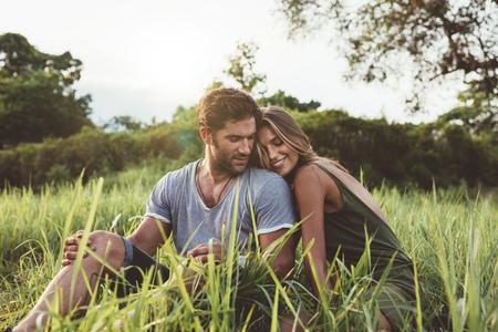 Tiro de jovem e mulher sentados juntos ao ar livre no campo de grama. Jovem casal romântico no prado.