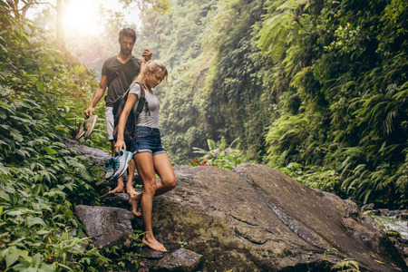 Shot of young couple walking through the mountain trail. Man and woman hiking on mountain trail barefoot.