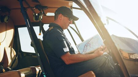 helicopter pilot: Male pilot sitting in the cockpit of a helicopter and reading flight map. Helicopter pilot reading air map. Stock Photo