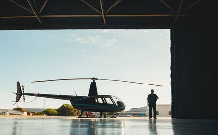 hangar: Full length image of pilot with a helicopter in an airplane hangar.