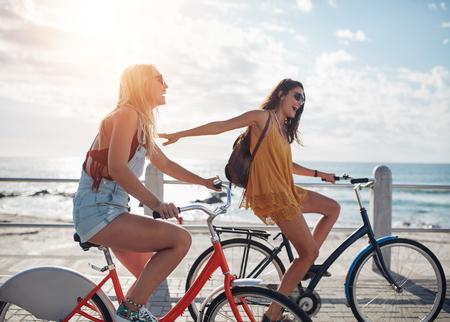 Ujęcie dwóch przyjaciół na przejażdżkę rowerem na promenadzie. Młode kobiety jazdy rowerów na nadmorskiej drodze w słoneczny dzień. Zdjęcie Seryjne
