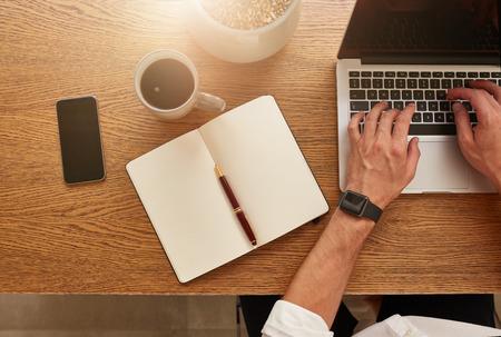 그의 책상에서 일하는 사업가의 상위 뷰. 노트북, 스마트 폰, 일기 및 커피 컵 현대 직장. 스톡 콘텐츠