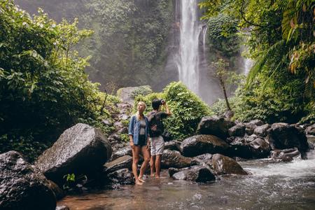 ヤング カップル ストリームによって立っている滝の写真を撮る男。自然の中を楽しんでいる観光客のカップル。