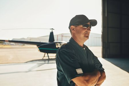 Portrait of helicopter pilot in uniform standing with his arms crossed and looking away with a helicopter in background