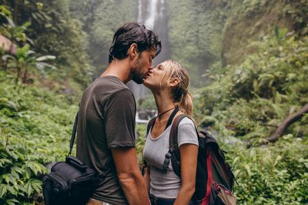 若いカップルが森の中に立っている間キスを愛するのショット。フォレスト内の滝の近くにキス愛のカップル。 写真素材