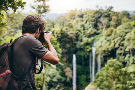 Hombre con mochila de pie delante de la cascada y tomando una foto. Macho caminante fotografiando una hermosa caída de agua en el bosque