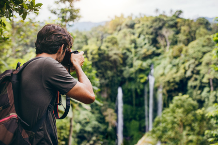 Man with backpack standing in front of waterfall and taking a photo. Male hiker photographing a beautiful water fall in forest