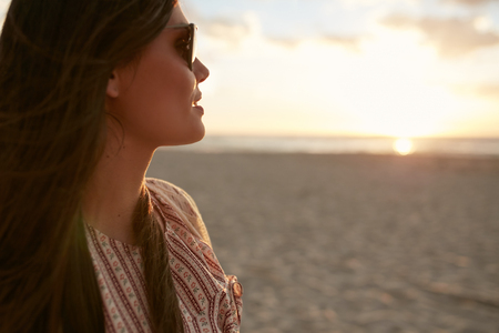 Close up shot of attractive young female with sunglasses looking at sunset on the beach. Female model on the sea shore at sunset. Imagens
