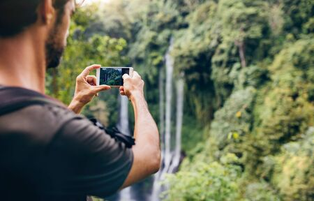 cellphones: Close up of a man taking photos of waterfall with his cellphone. Male hiker photographing a water fall in forest.