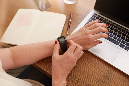 personal data assistant: Close up of smartwatch on womans hand, she is using the smart wrist watch while sitting at her work desk.