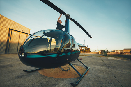 rotor: Image of pilot checking the helicopter rotor blades at the airfield. Man inspecting his aircraft before a flight. Stock Photo