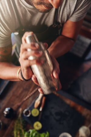 cocktail: Close up shot of male bartender mixing drink in cocktail shaker Stock Photo