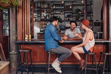 Group of young friends sitting and talking at a cafe. Young men and women meeting in a coffee shop.