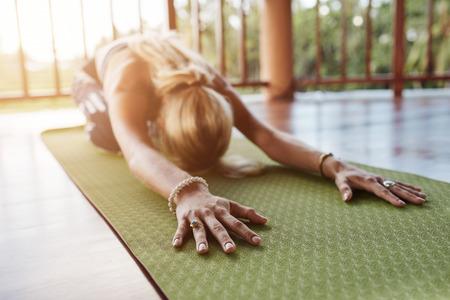 앞으로 스트레칭, 운동 매트에 요가 포즈를 수행하는 여자. 피트 니스 여성 체육관에서 balasana 요가 수행 손에 초점.