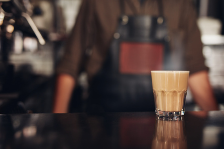 glass cup: Shot of cup of coffee on counter with barista standing in background.