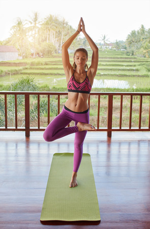 joined: Young beautiful female doing yoga tree pose. Healthy young woman standing on one leg with hands joined overhead.