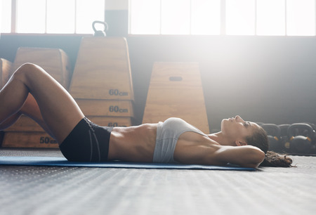 WOMAN FITNESS: Side view image of fitness woman doing sit ups on an exercise mat. Muscular young woman lying on exercise mat with her hands behind head doing stomach exercises. Stock Photo