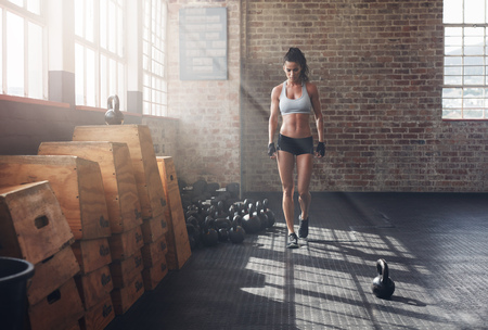 Full length shot of fitness woman walking in the gym with kettle bell on floor. Female athlete warming up before a intense fitness training. Stock Photo