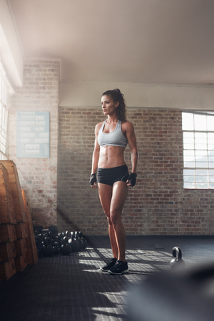 strong woman: Full length shot of strong woman standing in crossfit gym and looking away. Confident fitness female model in sportswear.