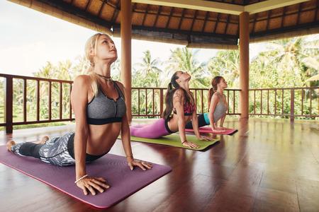 Disparo de jóvenes mujeres que realizan cobra plantean en estera de ejercicio en clase de yoga. Tres mujeres haciendo base estiran en la estera de fitness.