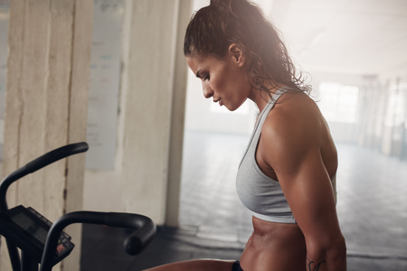 Side view close up shot of muscular woman exercising on gym bike. Female in sportsbra looking focused during her physical training at health club. Stock Photo
