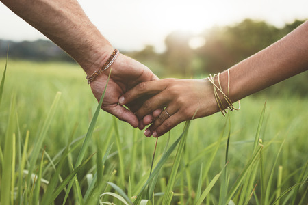 Shot of romantic couple holding hands in a field. Close up shot of man and woman with hand in hand walking through grass field.