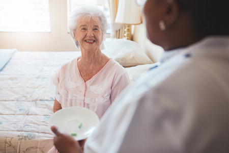 Indoor shot of senior woman sitting on bed and home care nurse giving medication. Caucasian elderly woman smiling.