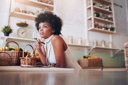 mujer pensando: tiro bajo techo de propietario bar de zumos mujer africana joven mirando a otro lado y pensar, ella está de pie detrás del mostrador del bar. Foto de archivo