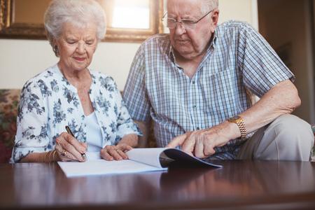 Retrato de alto el marido y la mujer haciendo papeleo juntos en casa. Jubilados par de firma de documentos.