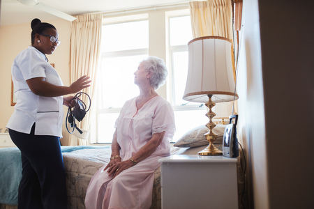 Indoors shot of home caregiver talking with senior woman sitting on bed. Female doctor visiting her senior patient at home.