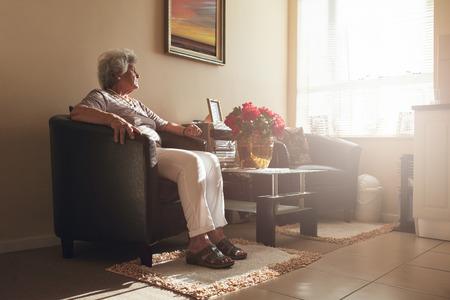 Senior vrouw zit alleen op een stoel thuis. Gepensioneerde vrouw ontspannen in de woonkamer.
