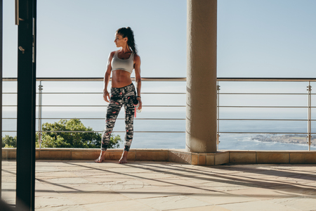 Full length shot of fit young woman standing in the balcony of her apartment and looking away. Fitness female model in sportswear relaxing after workout.