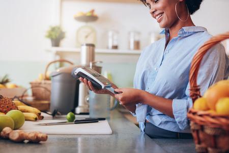 카드 판독기 컴퓨터에서 신용 카드를 스와핑 주스 바에서 여성 직원. 아프리카 여자 체크 아웃 카운터에 서 서입니다. 스톡 콘텐츠