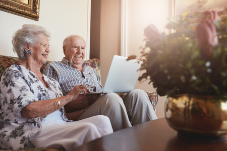 Portrait of smiling senior couple sitting together at home and surfing internet on laptop. Old man and woman relaxing on a sofa with a laptop computer.