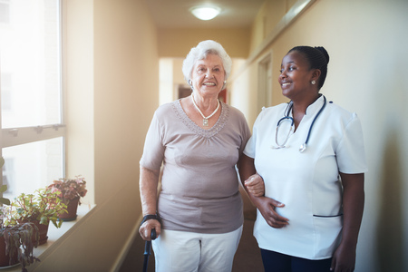 Happy healthcare worker and senior woman together at nursing home. Caring female doctor assisting a senior patient to walk. Stock Photo