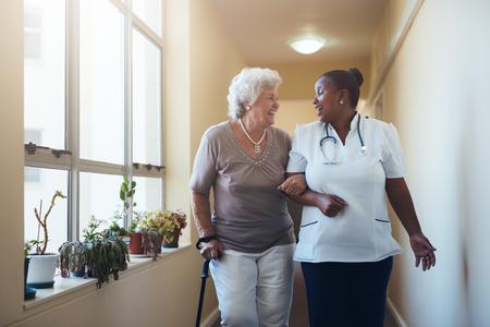 Portrait von Beschäftigten im Gesundheitswesen zu Fuß lächelnd und spricht mit älteren Frau. Glückliche ältere Frau bekommt für einen Spaziergang durch Pflegeheim von Krankenschwester helfen.