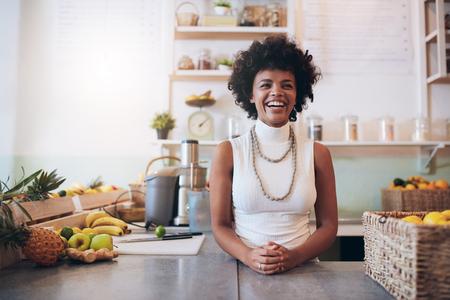 Retrato da mulher africana nova que está atrás do contador da barra de suco que olha a câmera e o sorriso. Proprietário feliz do bar de suco.