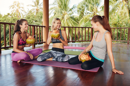 people together: Three young women sitting together at yoga class and drinking green coconut juice. Group of people taking a break from yoga workout.
