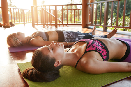 Shot of beautiful young woman lying in yoga class. Young people relaxing in corpse pose at health center. Stock Photo