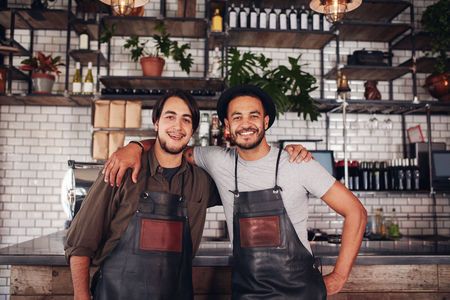 Portrait of two young coffee shop partners standing together at the counter. Happy young male bartenders.