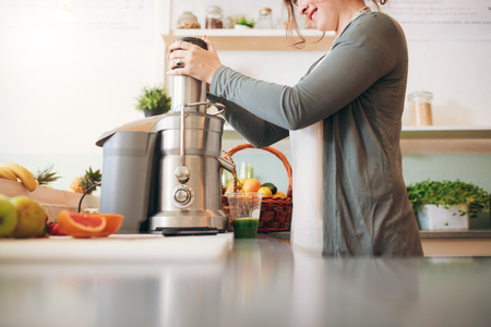 cropped shot: Cropped shot of  young female bar employee making fruit juice using juicer machine at counter. Stock Photo
