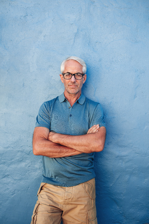 Vertical portrait of confident mature man standing against a blue background. Handsome caucasian man in glasses standing with his arms crossed against a wall.