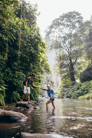 outdoor shot: Outdoor shot of young man helping woman crossing stream. Couple in forest crossing the creek. Stock Photo