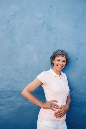 senior female: Portrait of attractive mature woman posing to camera against blue background. Middle aged female standing with her hands on hips and looking at camera smiling.