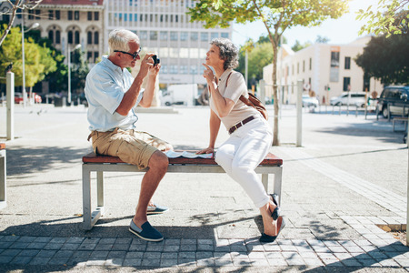 taking a wife: Side view of mature man photographing his wife. Senior couple sitting outdoors on a bench taking pictures of each other with digital camera.